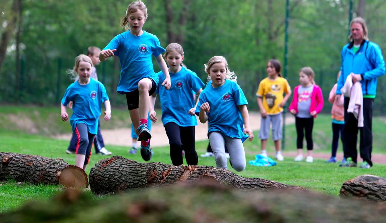 Kinder laufen und springen über eine Wiese auf der Baumstämme liegen
