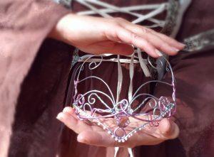Frau im Gewand hält Krone.