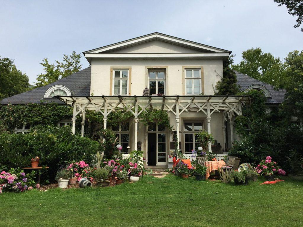 Ein Haus mit Veranda und vielen Blümenkübeln.