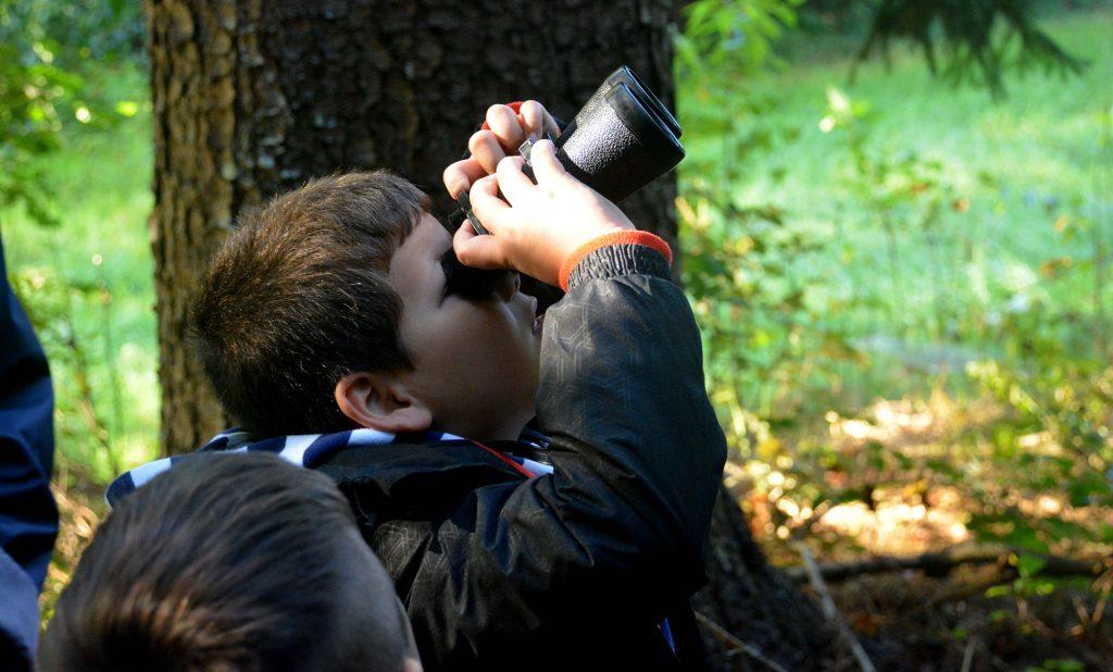 Ein Kind blickt durch ein Fernglas.