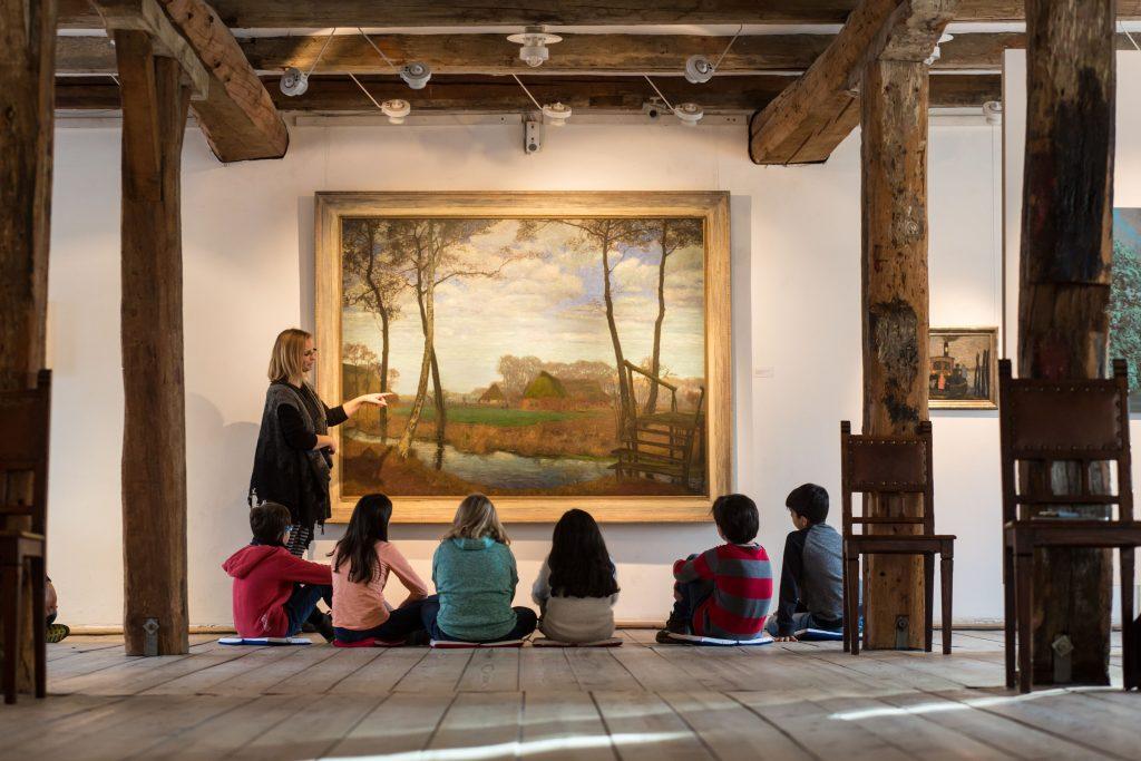 Kinder sitzen in einer Reihe und schauen ein Bild an