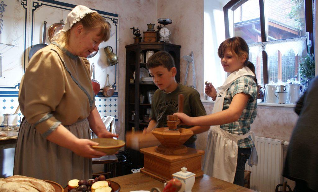 Eine Frau und zwei Kinder, verkleidet in Kleidung von ca. 1900 in einer ebenfalls altertümlichen Küche.