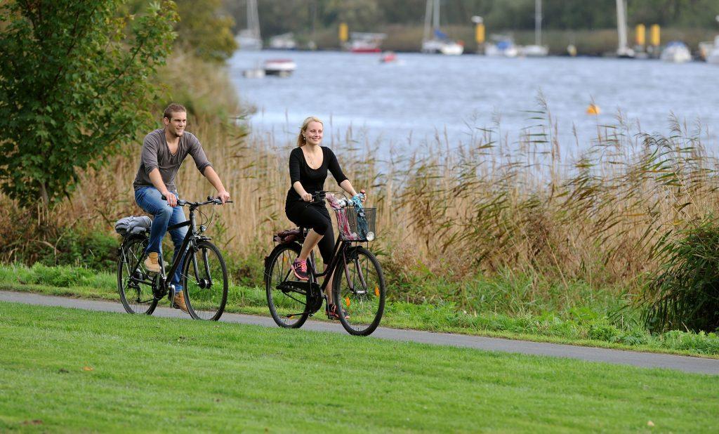 Ein Radfahrer und eine Radfahrerin radeln entlang des Weser-Ufers