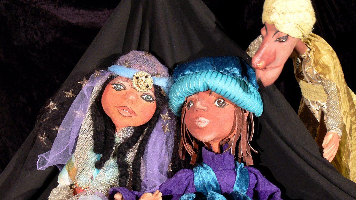 Eine weibliche und zwei männliche Puppen sitzen vor einem schwarzen Vorhang.