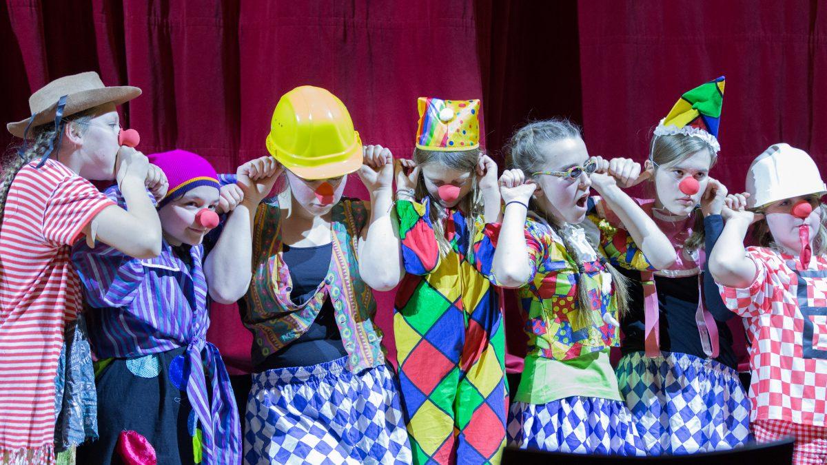 Auf einer Bühne stehen sieben als Clowns verkleidete Kinder.