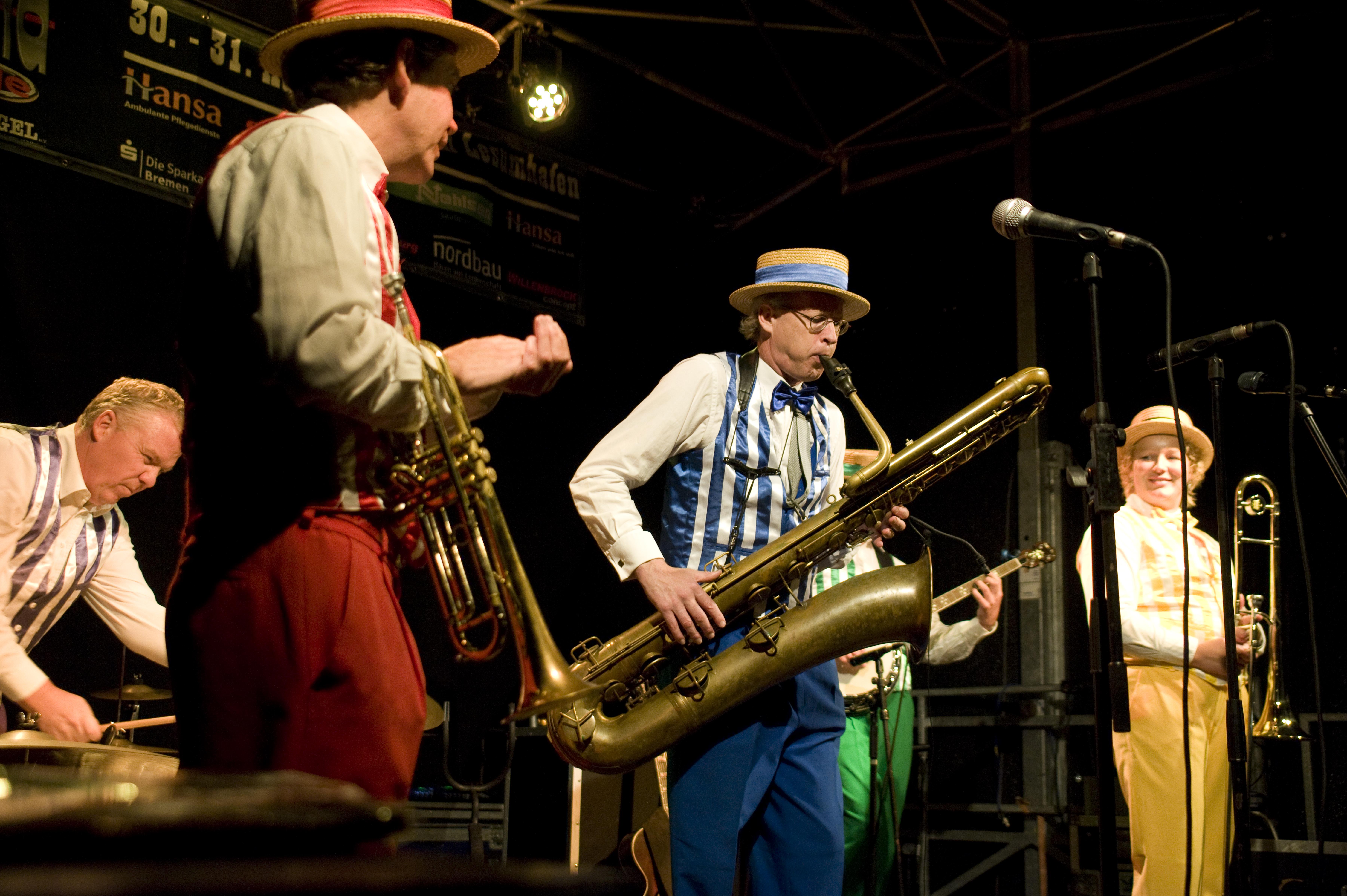 Musiker auf der Bühne, im Fokus ein Tuba spielender Mann