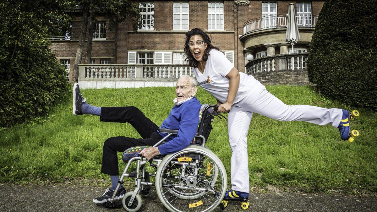 Pflegerin in Rollschuhen schiebt im Rollstuhl sitzenden Mann.