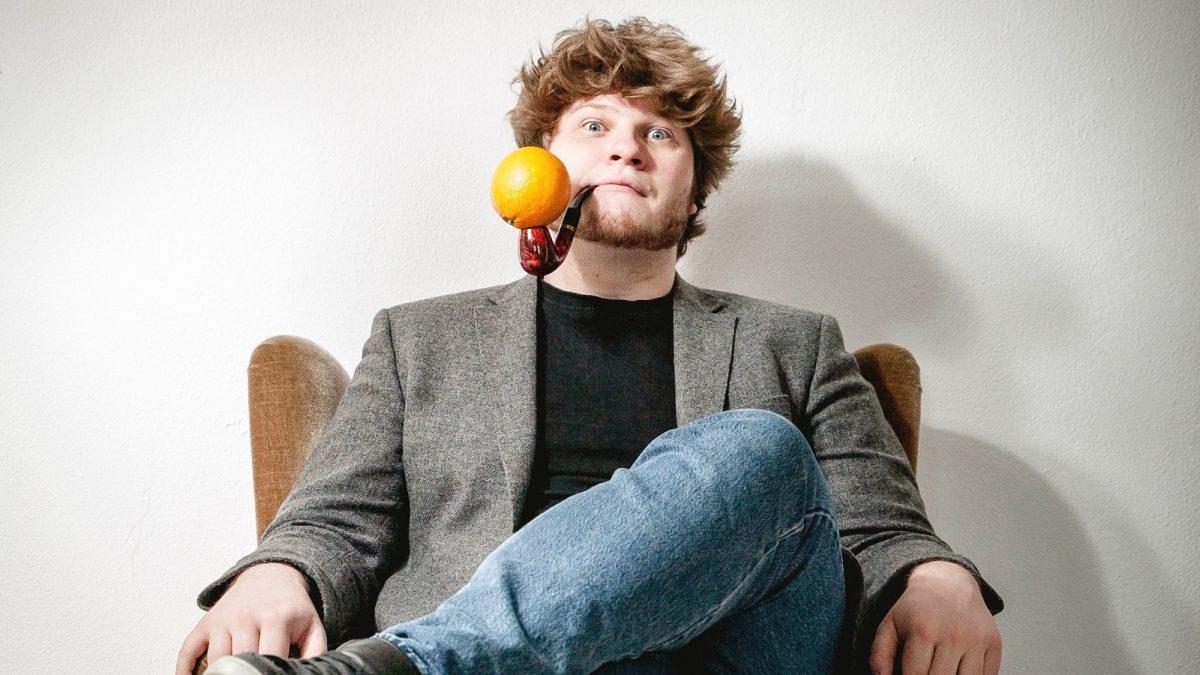Mann mit Pfeiffe und daraufliegender Orange sitzt auf einem Sessel.