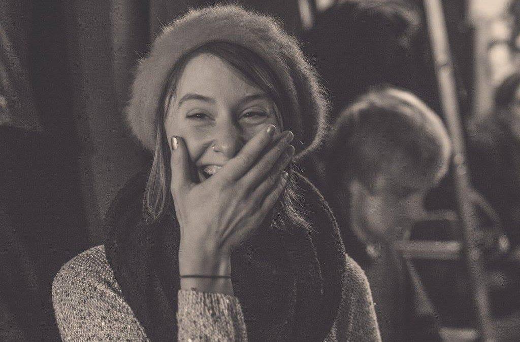 Frau hält lachend die Hand vor den Mund