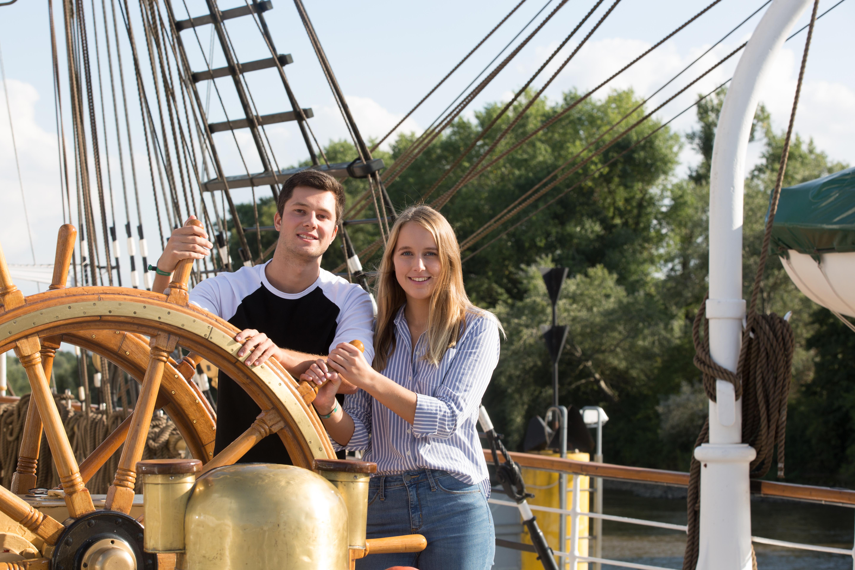 Junger Mann und junge Frau gemeinsam am Steuer eines Segelbootes