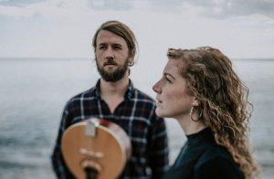 Mann mit Gitarre und Frau stehen am Wasser