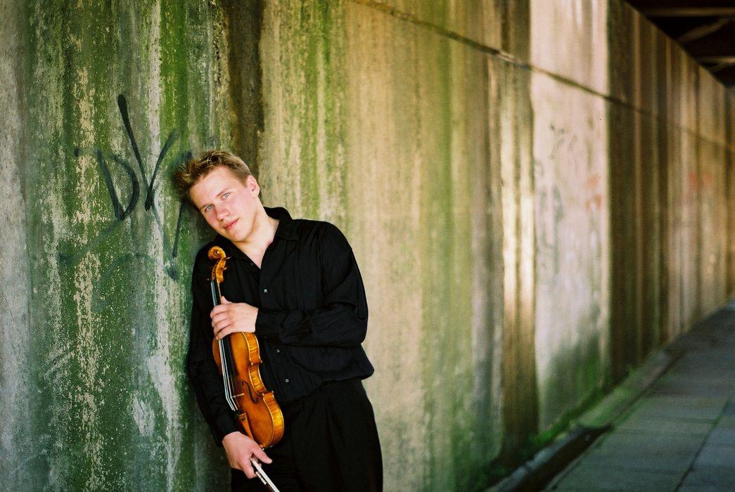 Junger Mann lehnt sich mit einer Violine an die Wand