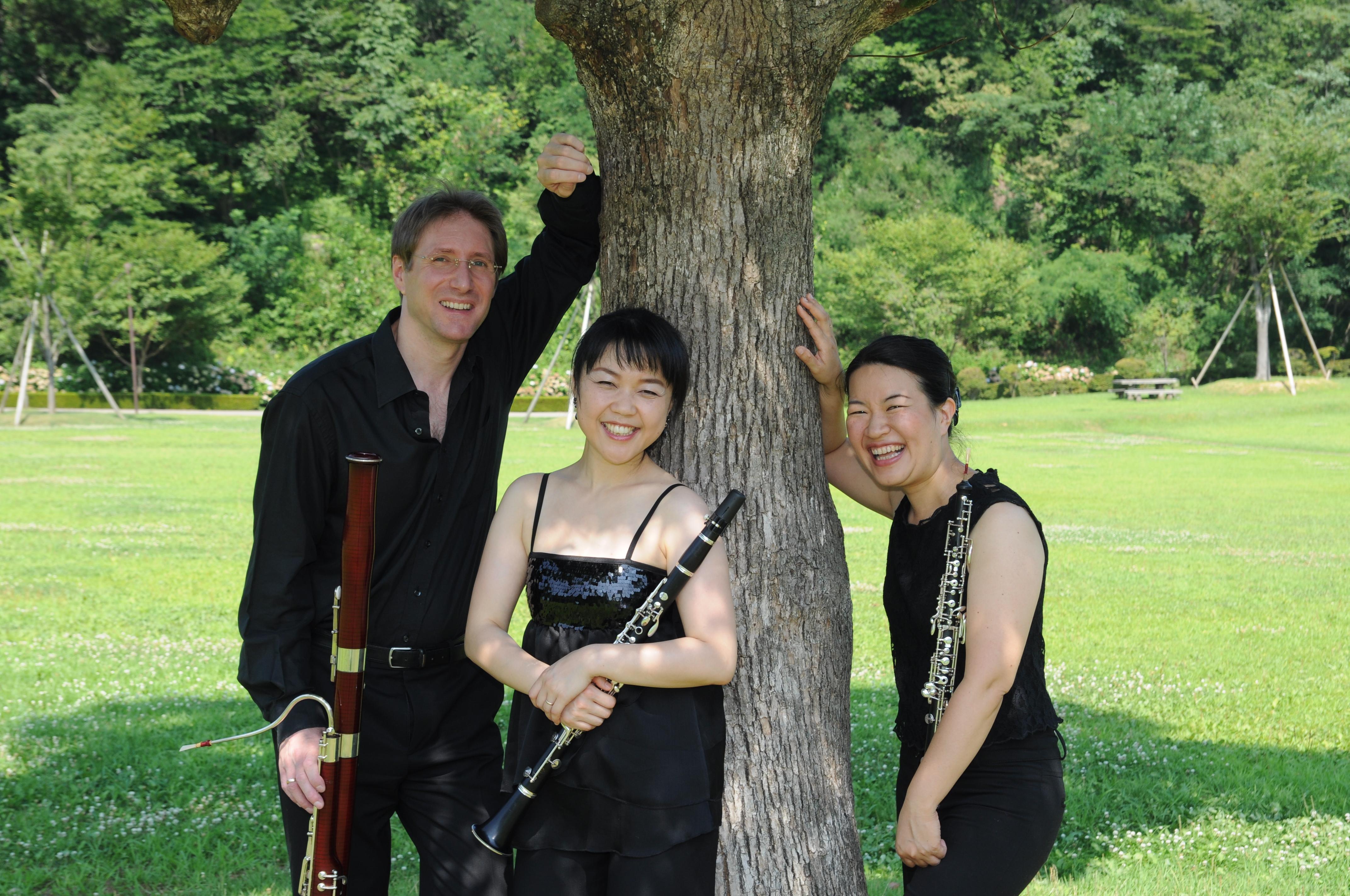 An einem Baum gelehnt stehen zwei Frauen und ein Mann und haben Blasinstrumente in der Hand.