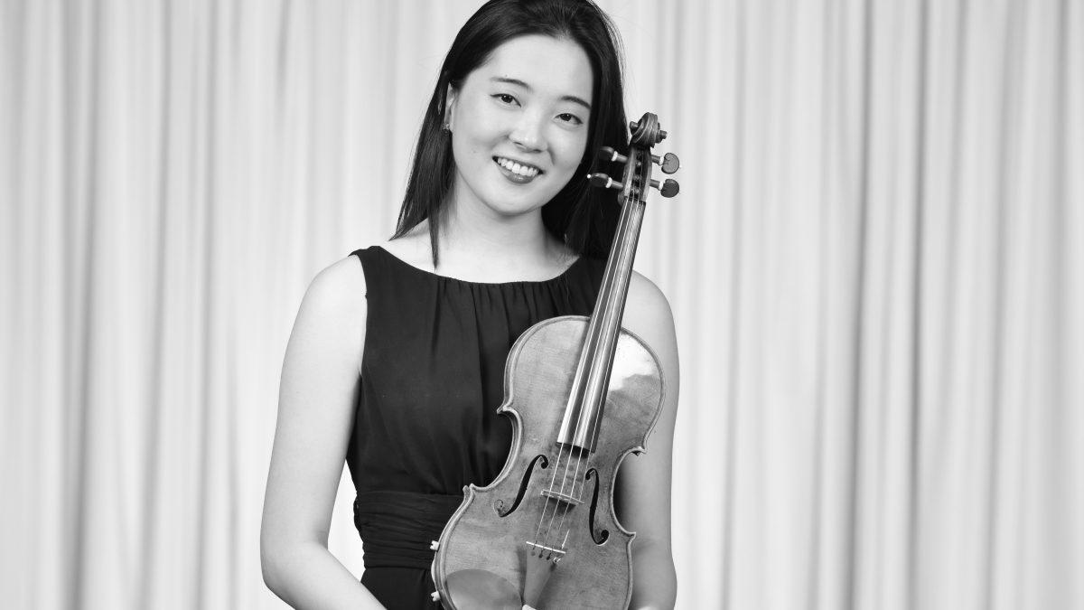 Junge Frau hält eine Geige vor die Brust und lächelt in die Kamera