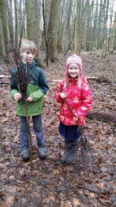 Junge und Mädchen mit Besen im Wald