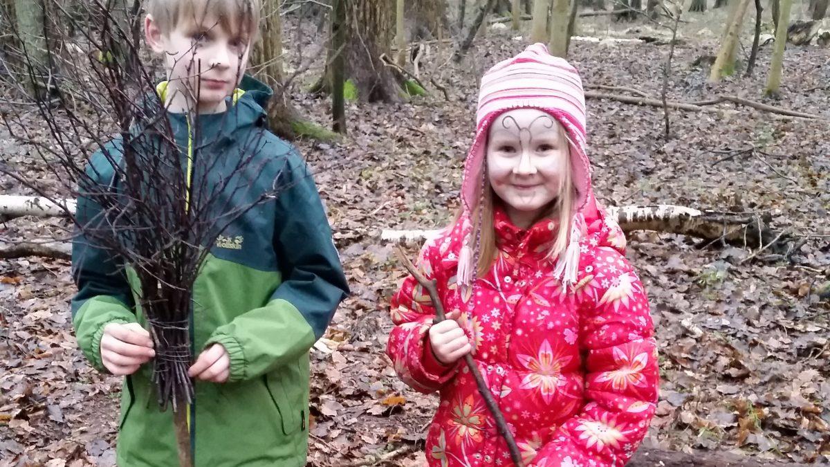 Junge und Mädchen im Wald mit selbstgebauten Besen