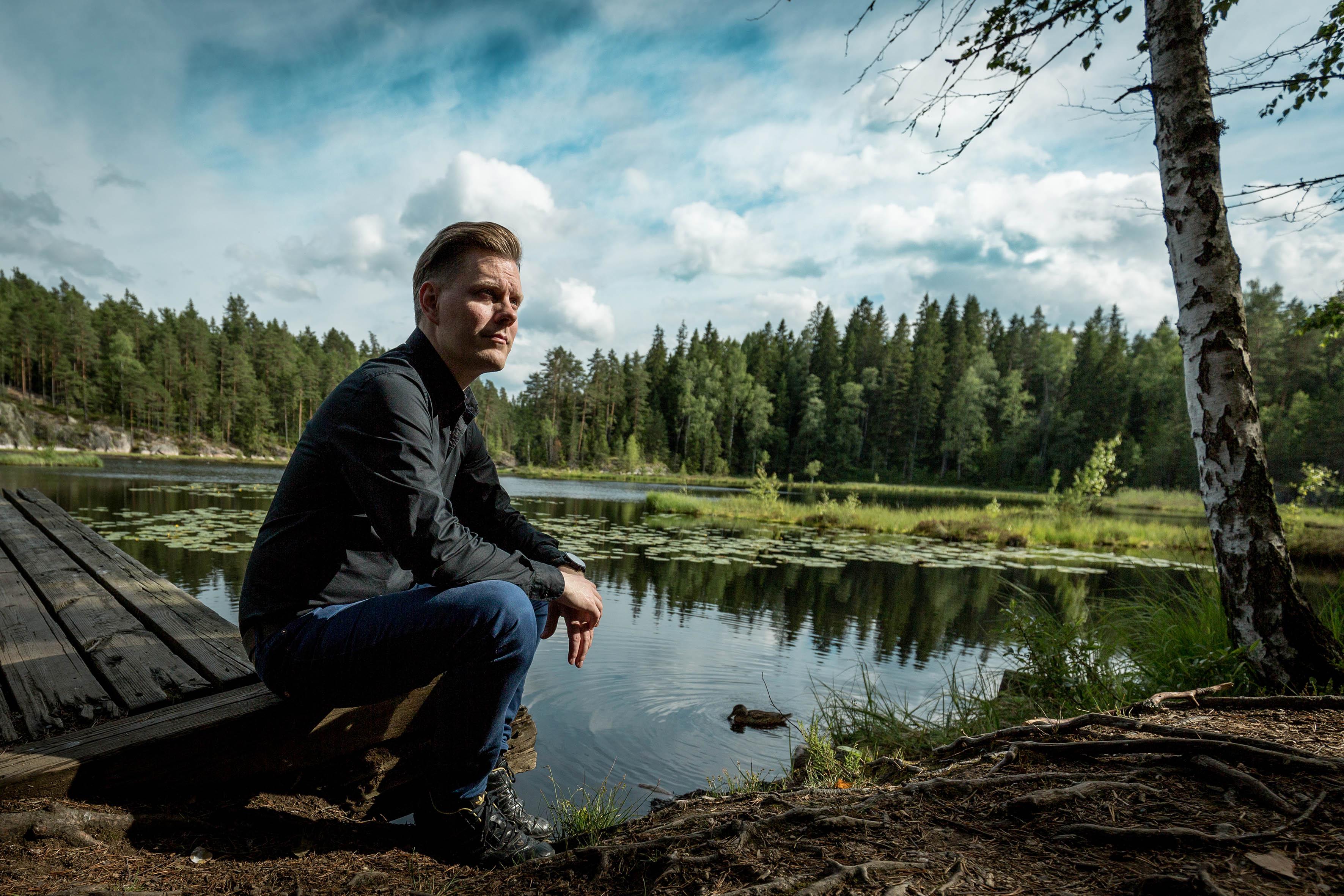 Mann hockt vor einem Teich und schaut in die Ferne