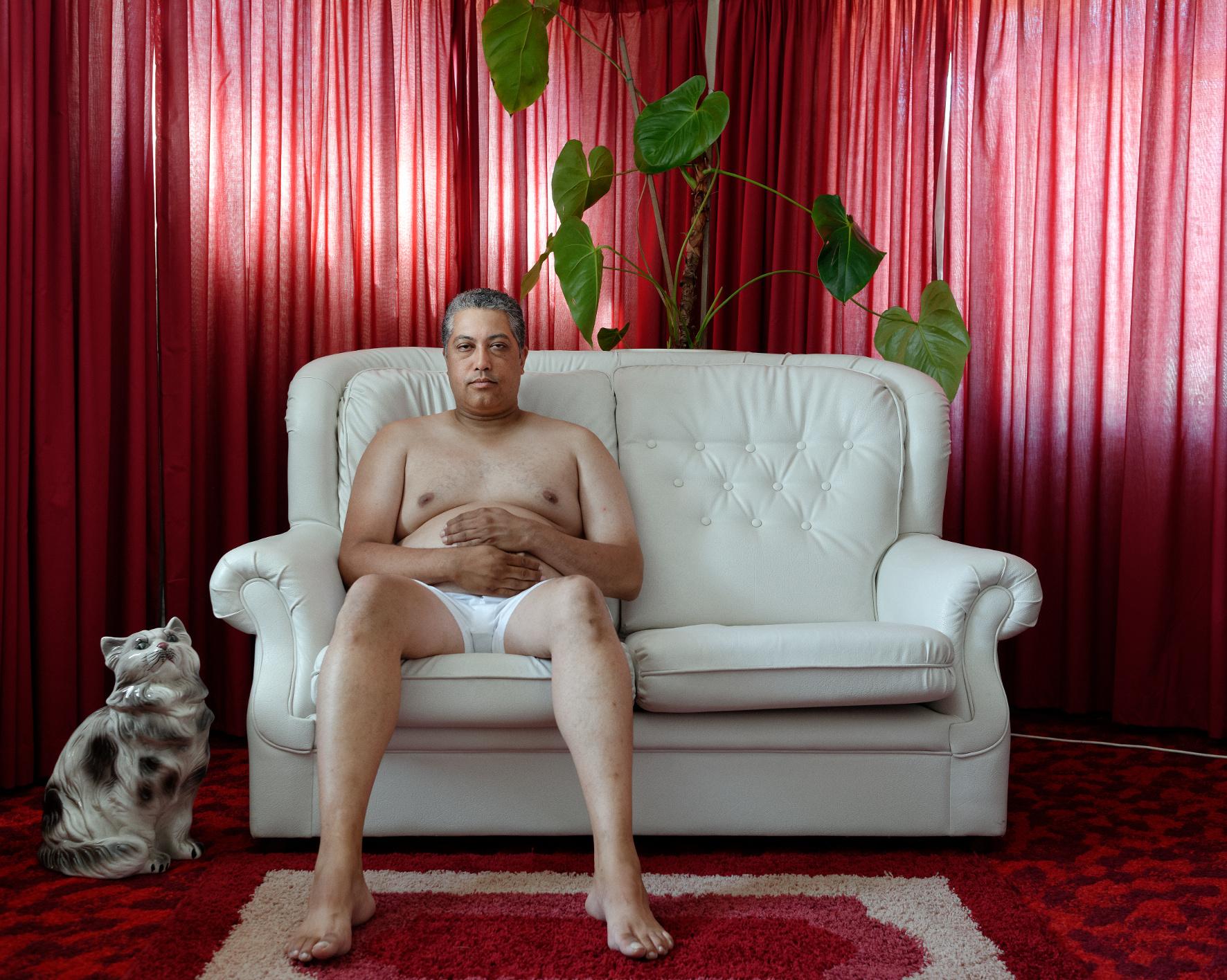 Mann sitzt in Unterhose aus hellem Sofa und hält sich die Hände vor den Bauch