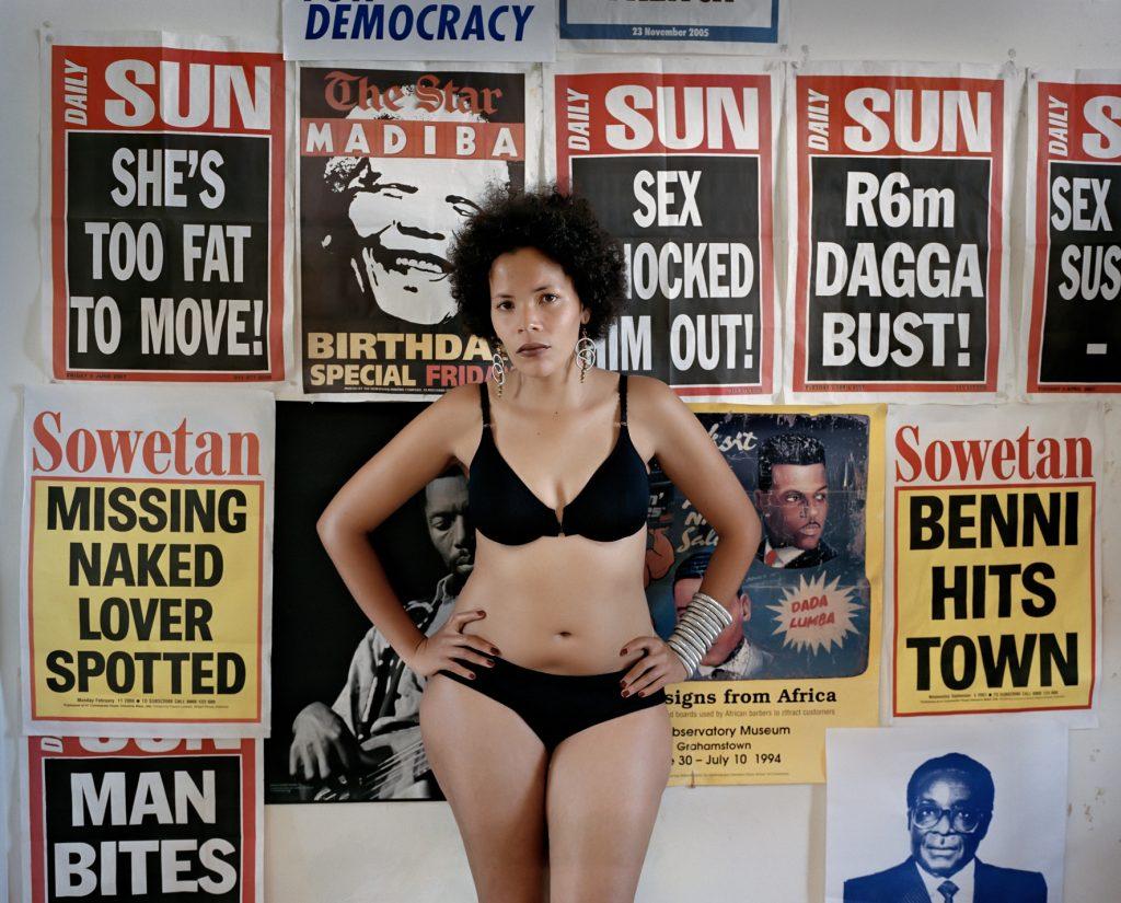 Frau steht in Unterwäsche vor einer plakatierten Wand