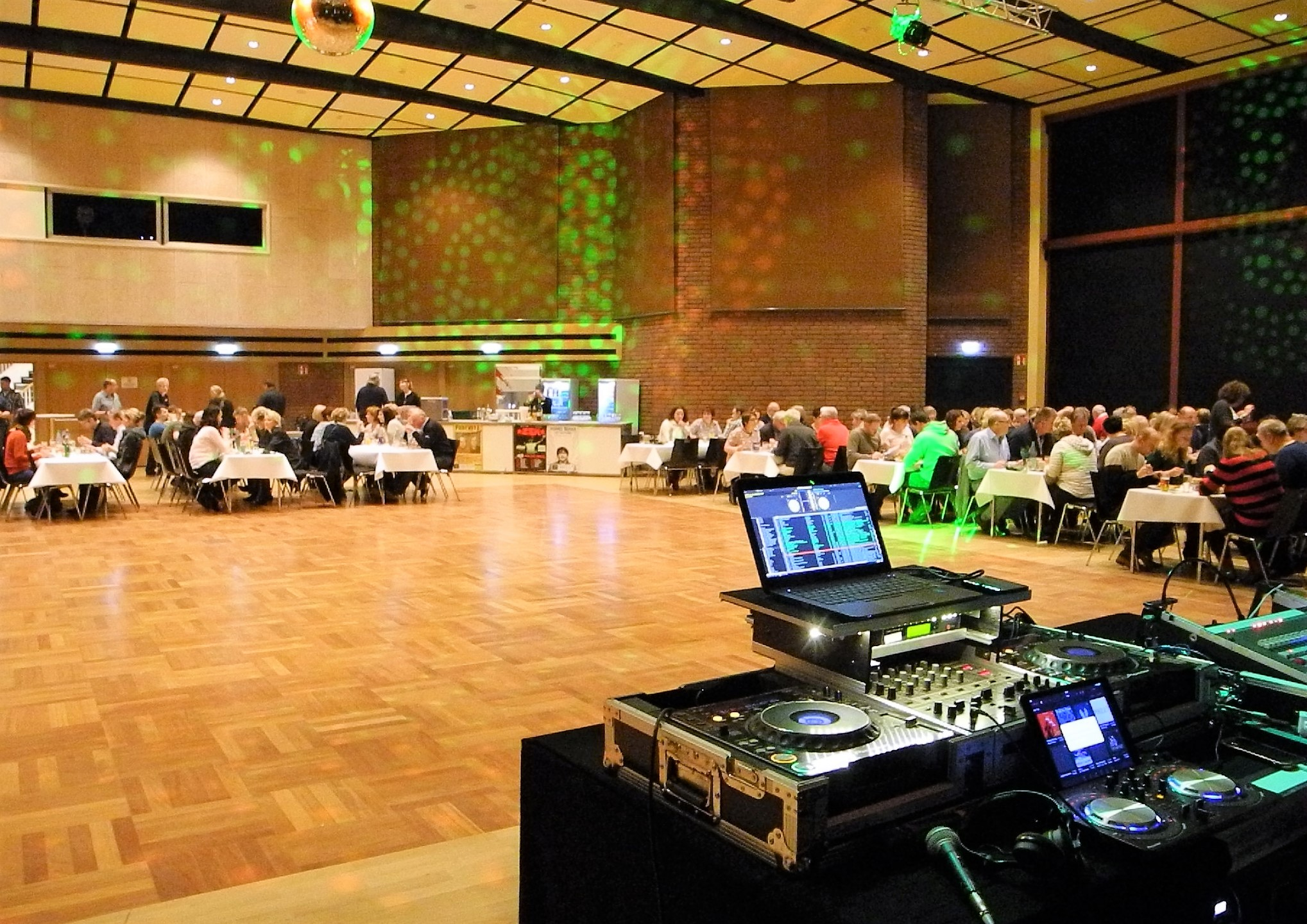 Ein DJ-Pult und viele an Tischen essende Menschen in einer großen Halle