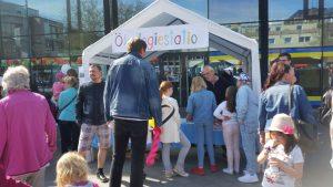 Erwachsene und Kinder versammeln sich vor einem offenen Zelt und lassen sich etwas von einem Mann erklären. Schriftzug am Zelt: Ökologiestation.