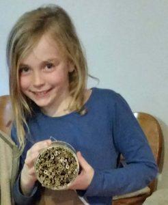 Mädchen hält eine Wildbienen Nisthilfe in der Hand