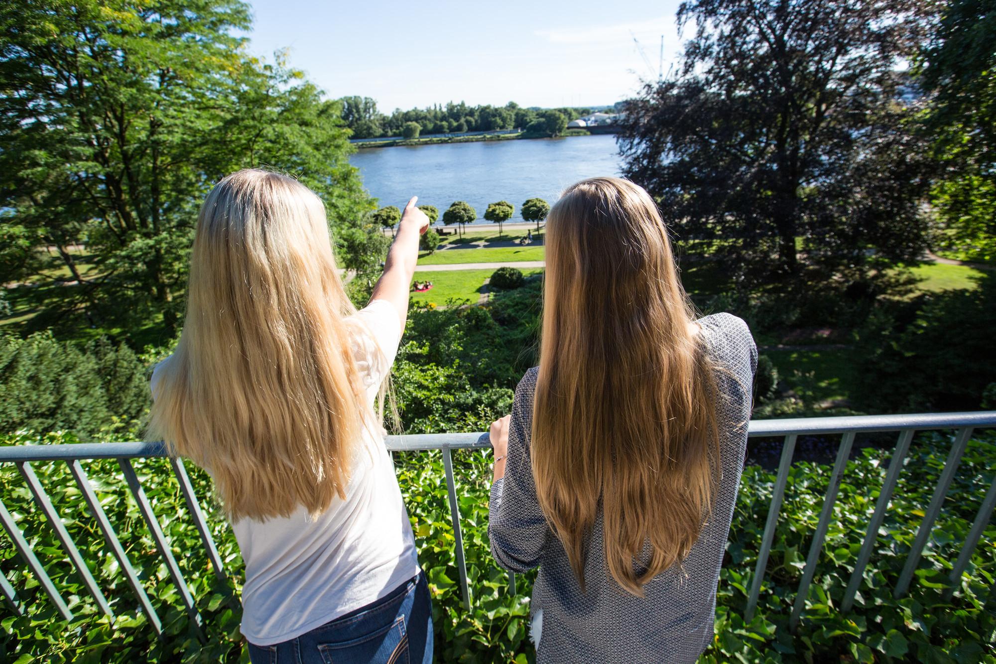 Zwei Frauen stehen am Geländer in einem Park und schauen in die Ferne. Die linke Frau zeigt mit dem Finger nach vorne.