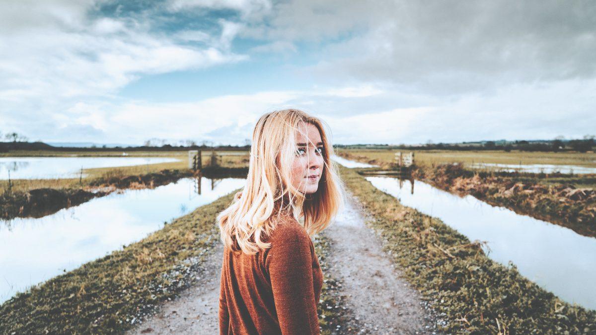 Frau dreht sich zur Kamera, im Hintergrund Natur und Gewässer