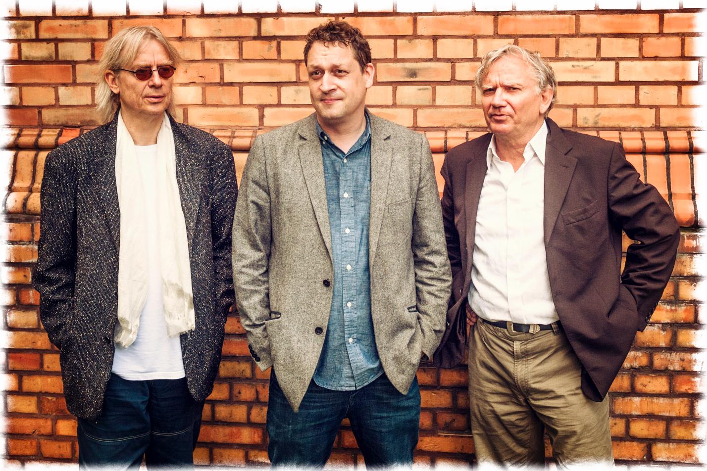 Drei Männer an einer Wand