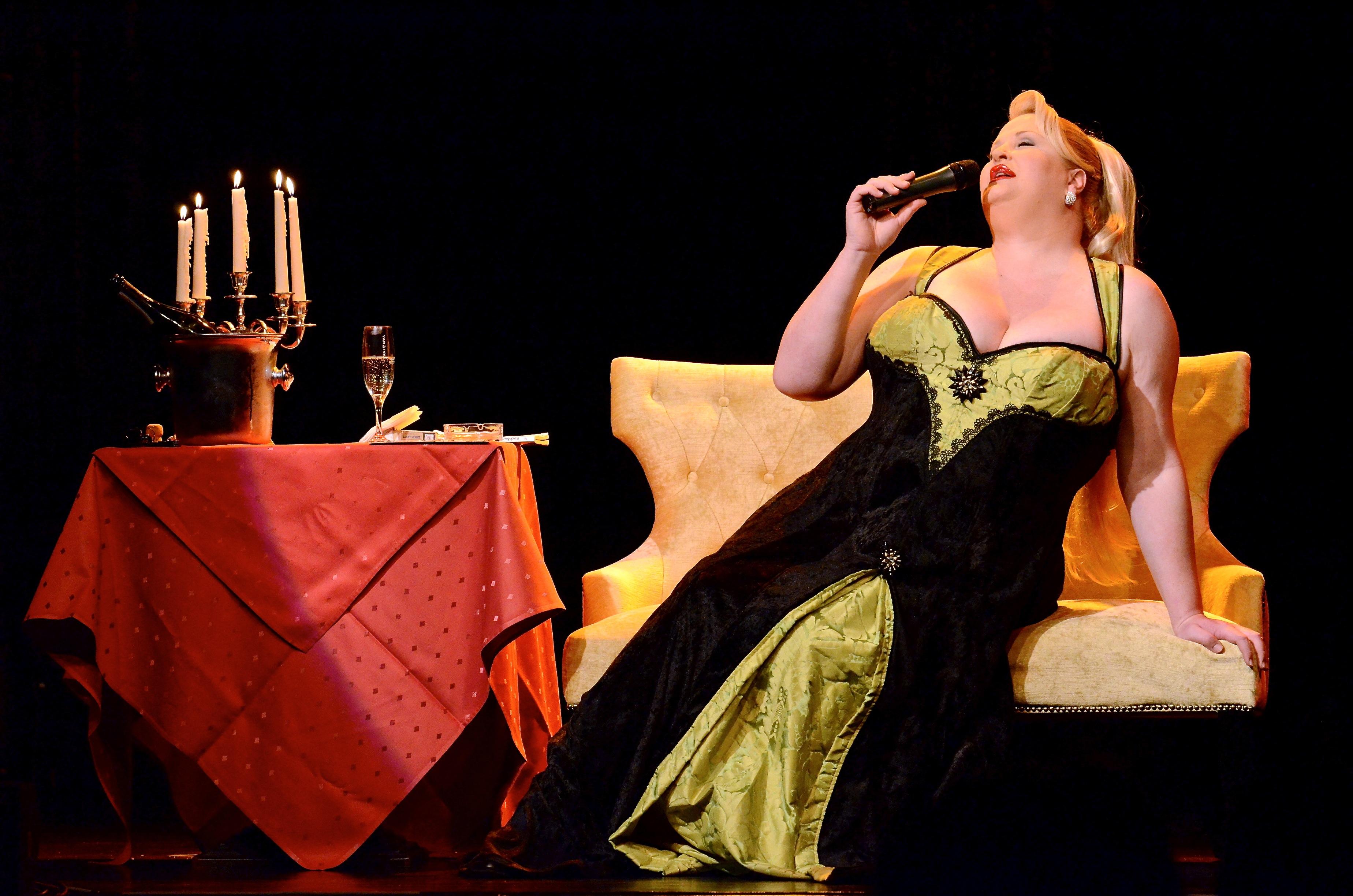 Frau auf der Bühne im einseidenen Kleid, hält ein Mikro an den Mund und lehnt sich auf der Couch zurück.