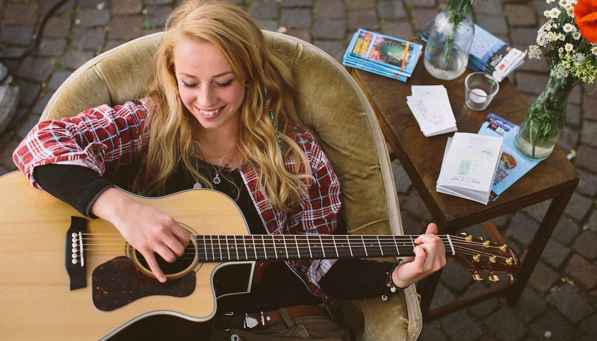 Frau sitz auf Sessel und spielt Gitarre