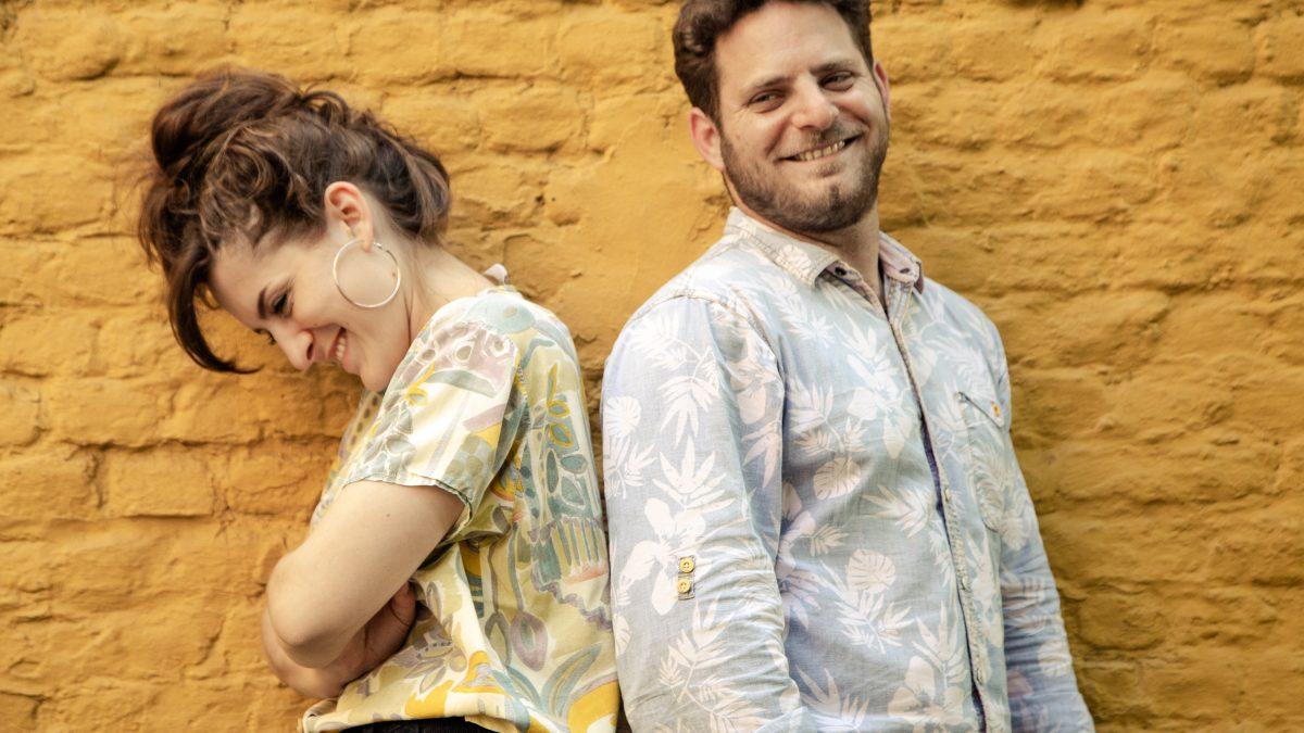 Mann und Frau lehnen sich vor einer Wand Rücken an Rücken.
