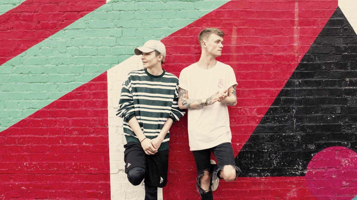 Zwei junge Menschen lehnen sich an eine bemalte Wand