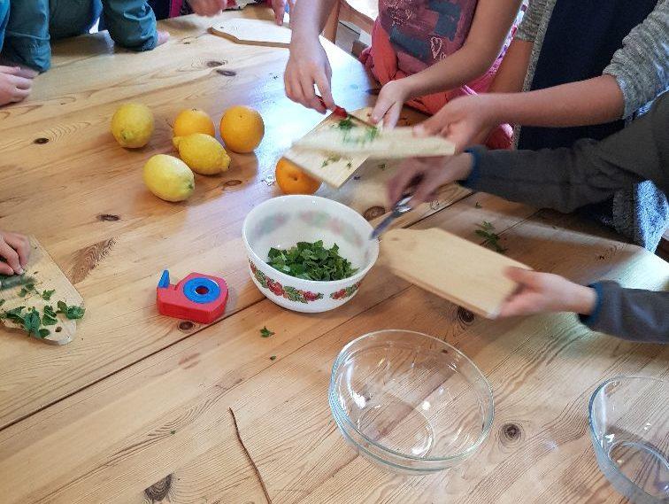 An einem Tisch werden Kräuter geschnitten und in einer Schüssel gesammelt