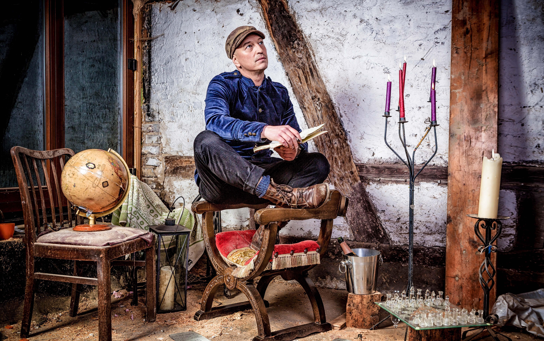 """Ein Mann sitzt im Schneidesitz auf der Armlehne eines Stuhls. Um ihn herum """"alte"""" Dinge"""