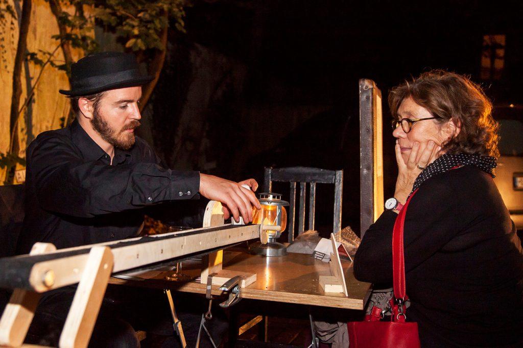 Mann und Frau sitzen sich am Tisch gegenüber, während der Mann etwas mit seinen händen festhält