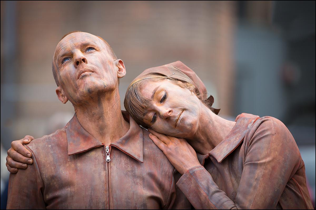 Wie Statuen angemalte Frau und Mann
