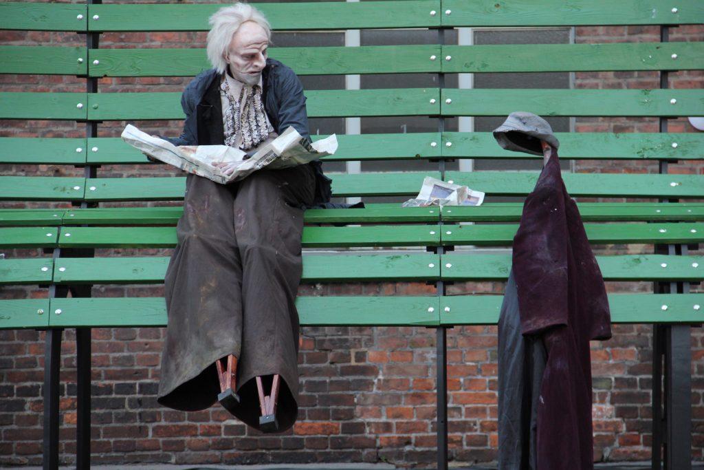 Mann sitzt mit Zeitung auf einer Bank und sieht einen Kleiderständer an