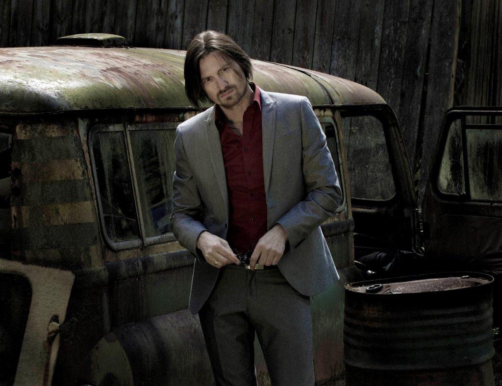 Ben Lorentzen im Anzug vor einem alten Wagen