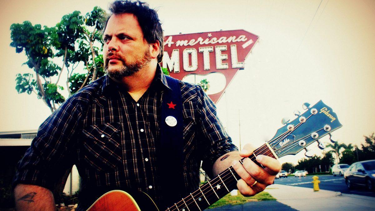 """Mann mit Gitarre steht vor einem """"Americana MOTEL"""" Schild"""