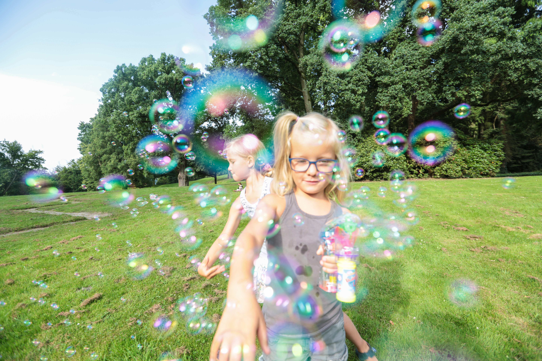 Zwei Mädchen spielen mit Seifenblasen im Park