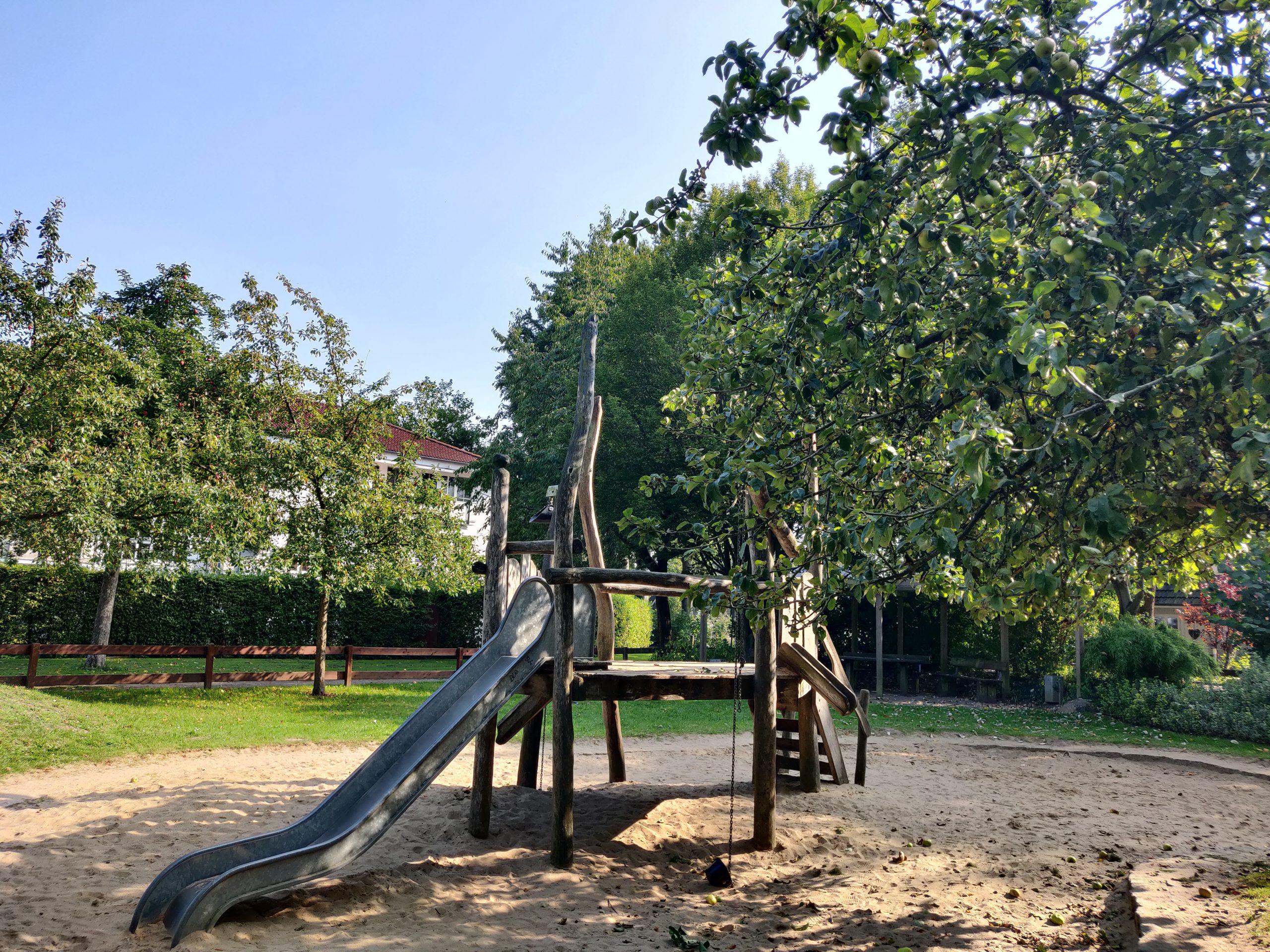 Spielplatz mit Klettergerüst und Apfelbaum
